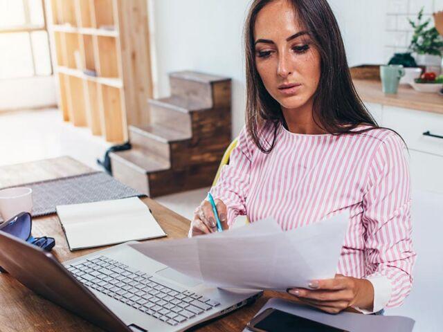 Mulher a trabalhar na cozinha de casa e a consultar as alterações no modelo da declaração recapitulativa de IVA