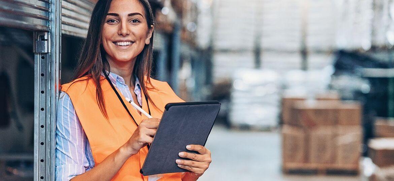 Joven empresaria trabajando en la digitalización de la logística en el almacén de la empresa