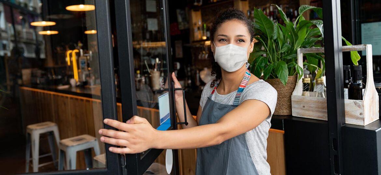 Mujer abriendo la puerta de su negocio después de disfrutar del Apoyo a la solvencia empresarial