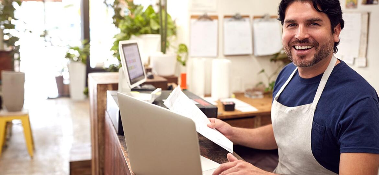 Hombre en su negocio consultando el diario de contabilidad y ingresando el libro diario y el libro mayor en el laptop