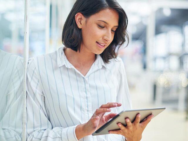 Mulher empresária a consultar na tablet as oportunidades da evolução digital para 2021
