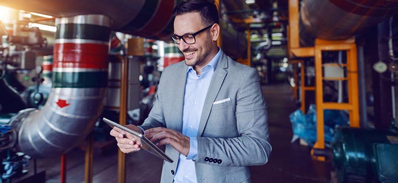 Homem gestor na fábrica a consultar no tablet o Sistema de Incentivos à Inovação Produtiva